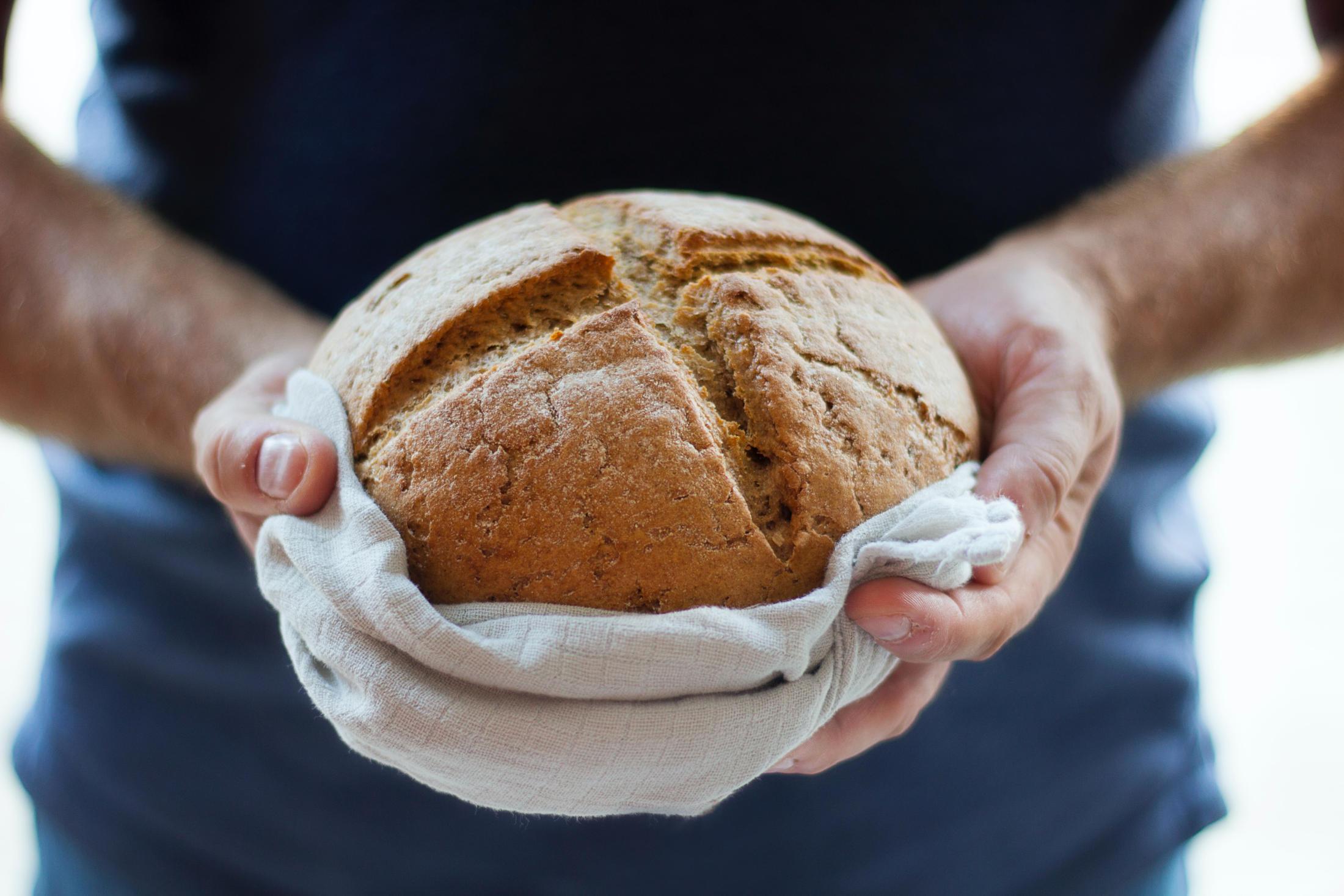 Hände halten ein Brot.