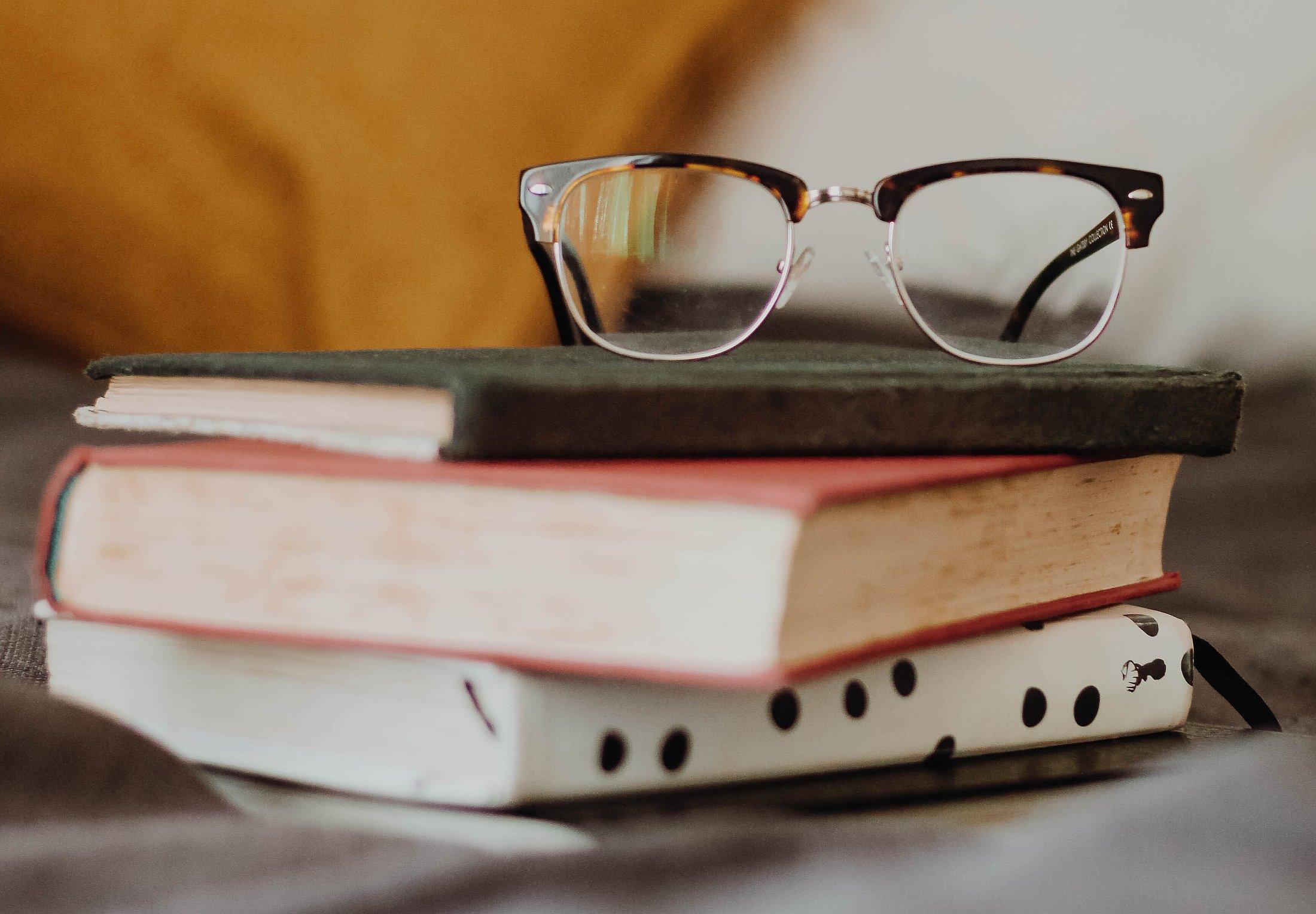 Ein kleiner Bücherstapel mit einer Brille